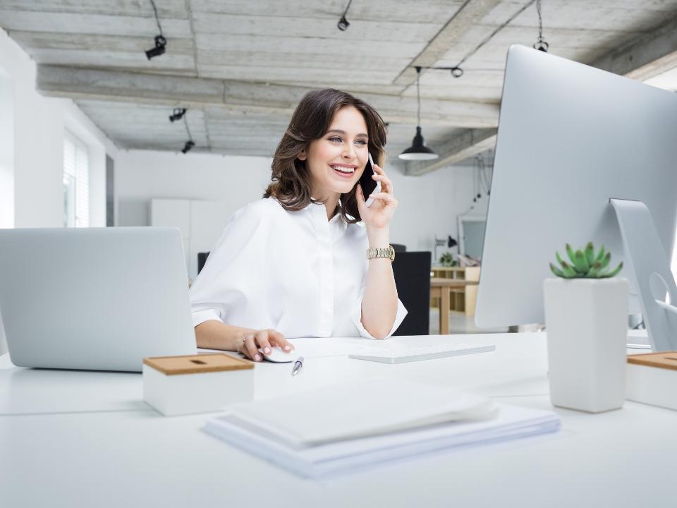 Uśmiechnięta kobieta rozmawia przez telefon